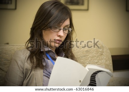 Portrait of a cheerful Business woman sitting on her desk holding a pen reading and signing documents