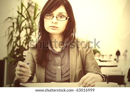 Portrait of a cheerful Business woman sitting on her desk holding a pen reading and signing documents - stock photo