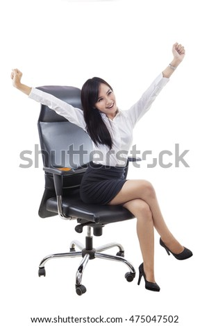 Portrait of a cheerful businesswoman sitting on the office chair while expressing her success by raising hands