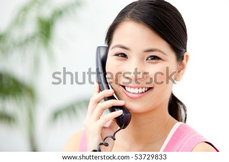 Portrait of a cheerful businesswoman talking on phone in the office - stock photo
