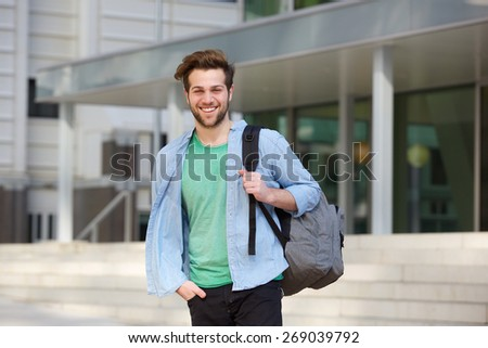 Portrait of a cheerful college student standing outside with back - stock photo
