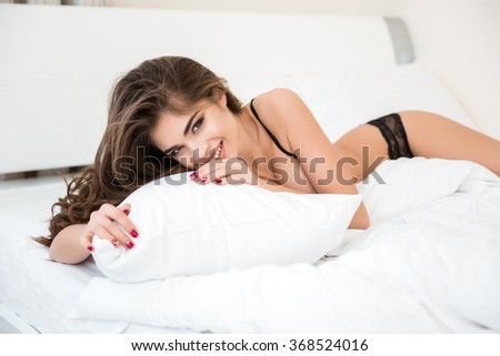 Portrait of a cheerful cute woman in sexy lingerie lying on the bed and looking at camera - stock photo