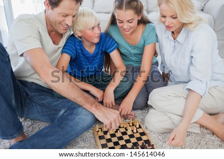 Portrait of a cheerful family playing chess lying on a carpet - stock photo