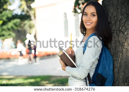 Portrait of a cheerful female teenager standing with backpack and notepad outdoors - stock photo