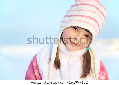 portrait of a cheerful girl walking around outdoors in the winter - stock photo