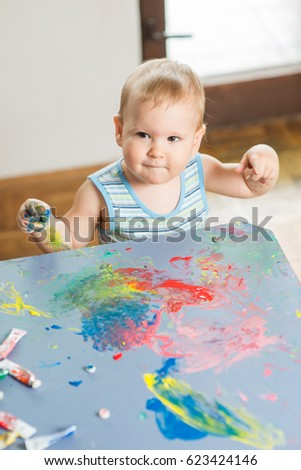 Portrait of a cheerful grimy kid. playing with paint