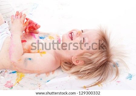 portrait of a cheerful grimy kid. playing with paint. on a white studio background. - stock photo