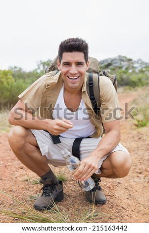 Portrait of a cheerful hiking man crouching on mountain terrain