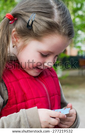 Portrait of a cheerful little baby girl in a red vest in the spring park - stock photo