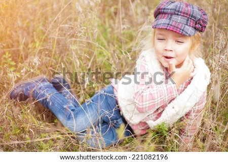 Portrait of a cheerful little girl in nature - stock photo