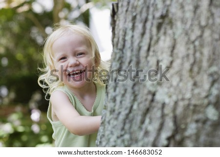 Portrait of a cheerful little girl peeking from behind tree - stock photo