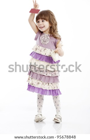 Portrait of a cheerful little girl with a bag and card