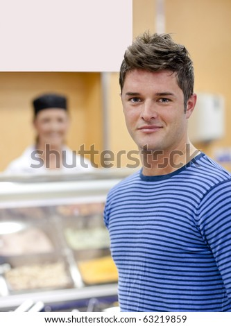 Portrait of a cheerful man choosing his lunch in the cafeteria of his campus - stock photo
