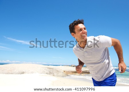 Portrait of a cheerful middle aged man running on the beach  - stock photo
