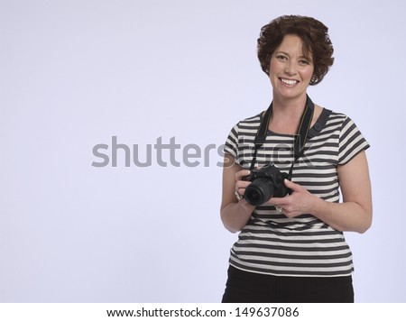 Portrait of a cheerful middle aged woman with digital camera against purple background - stock photo