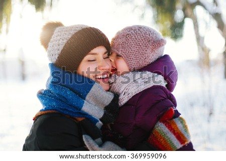 Portrait of a cheerful mother and her daughter in a winter forest at sunset. Focus on the child - stock photo