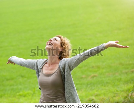Portrait of a cheerful older woman smiling with arms outstretched  - stock photo