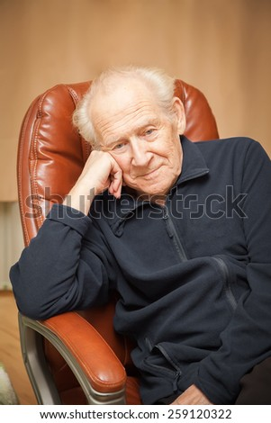portrait of a cheerful pensive old man with a head reclined upon his hand - stock photo
