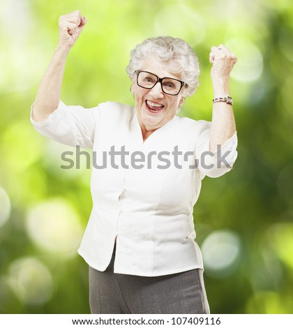 portrait of a cheerful senior woman gesturing victory against a nature background - stock photo