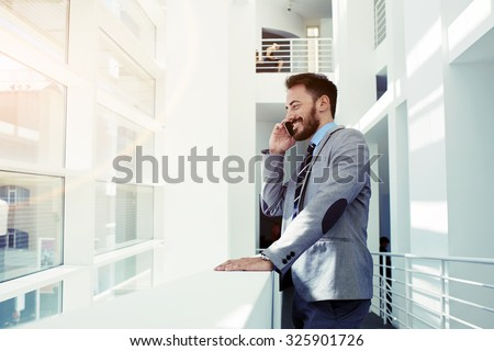 Portrait of a cheerful smiling men office worker talking on mobile phone while standing in modern office space, happy male entrepreneur having cell telephone conversation while resting after meeting  - stock photo