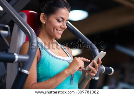 Portrait of a cheerful sports woman using smartphone in fitness gym - stock photo