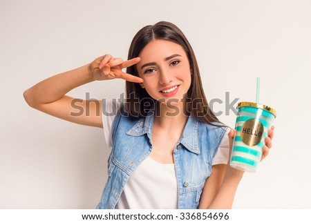 Portrait of a cheerful teenager girl drinking juice on a white background - stock photo
