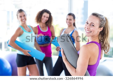 Portrait of a cheerful woman holding exercise mat in fitness studio - stock photo