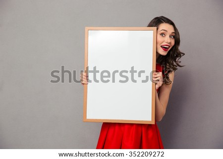 Portrait of a cheerful woman in red dress holding blank board over gray background - stock photo