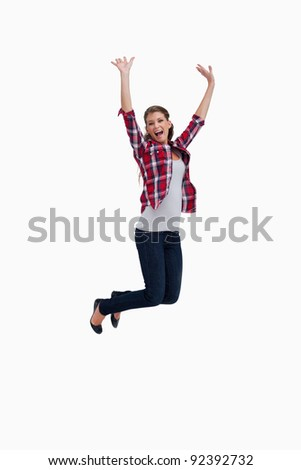 Portrait of a cheerful woman jumping against a white background - stock photo