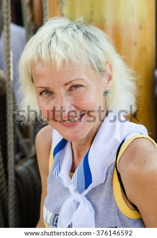 Portrait of a cheerful woman on sailboat - stock photo