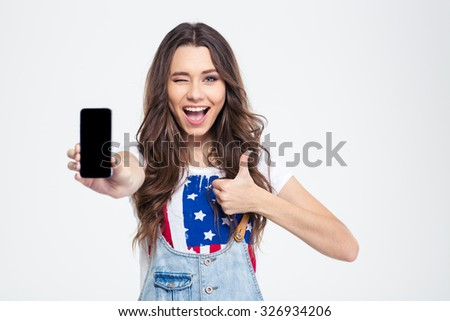 Portrait of a cheerful woman showing blank smartphone screen and showing thumb up isolated on a white background - stock photo