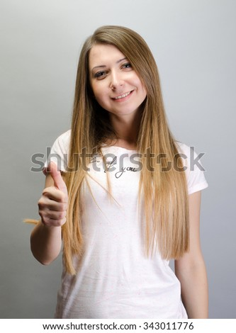 Portrait of a cheerful woman showing thumb up over gray background - stock photo
