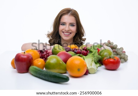 Portrait of a cheerful woman sitting at the table with fruits - stock photo
