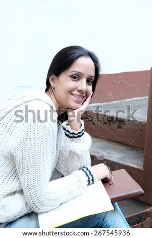 Portrait of a cheerful woman sitting with books on staircase. - stock photo