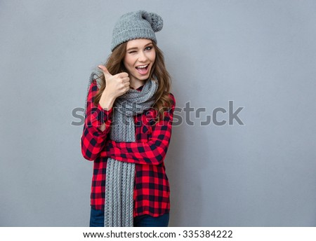 Portrait of a cheerful woman winking and showing thumb up on gray background - stock photo
