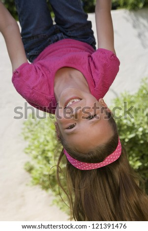 Portrait of a cheerful young girl enjoying while hanging upside down on a swing - stock photo