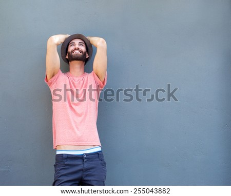 Portrait of a cheerful young man laughing on gray background - stock photo