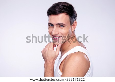 Portrait of a cheerful young man over gray background - stock photo