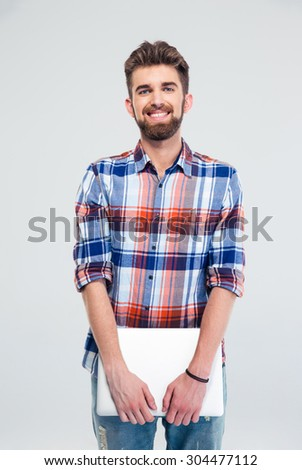 Portrait of a cheerful young man standing and holding laptop isolated on a white background. Looking at camera - stock photo