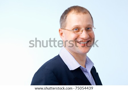 Portrait of a cheerful young man wearing glasses.