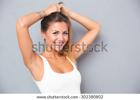 Portrait of a cheerful young woman holding her ponytail over gray background - stock photo