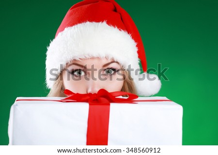 Portrait of a cheerful young woman in Santa hat looking at camera behind a x-mas giftbox on the foreground