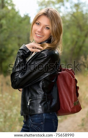 Portrait of a cheerful young woman in the forest - stock photo