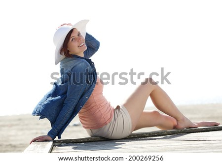 Portrait of a cheerful young woman relaxing at beach - stock photo