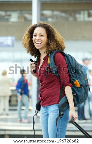 Portrait of a cheerful young woman smiling with luggage at airport - stock photo