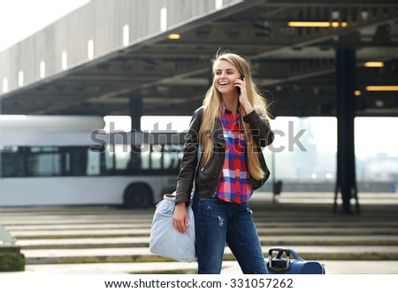 Portrait of a cheerful young woman standing at bus terminal with bags and mobile phone