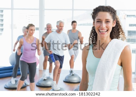 Portrait of a cheerful young woman with people exercising in the background at fitness studio