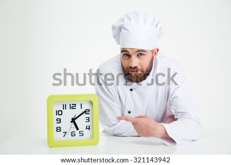 Portrait of a chef cook leaning on the table and pointing finger on clock isolated on a white background - stock photo