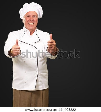 Portrait Of A Chef Cook With Hand Sign On Black Background - stock photo