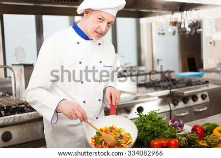 Portrait of a chef showing sliced vegetables in a pan - stock photo